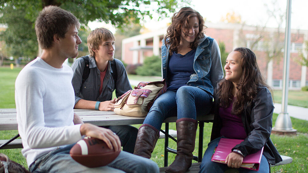 Students at Concordia talk while seated at a picnic table.