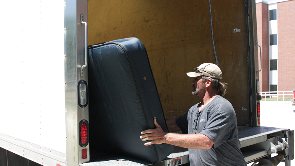 A man loads one of the mattresses Concordia donated to People's City Mission on July 13.