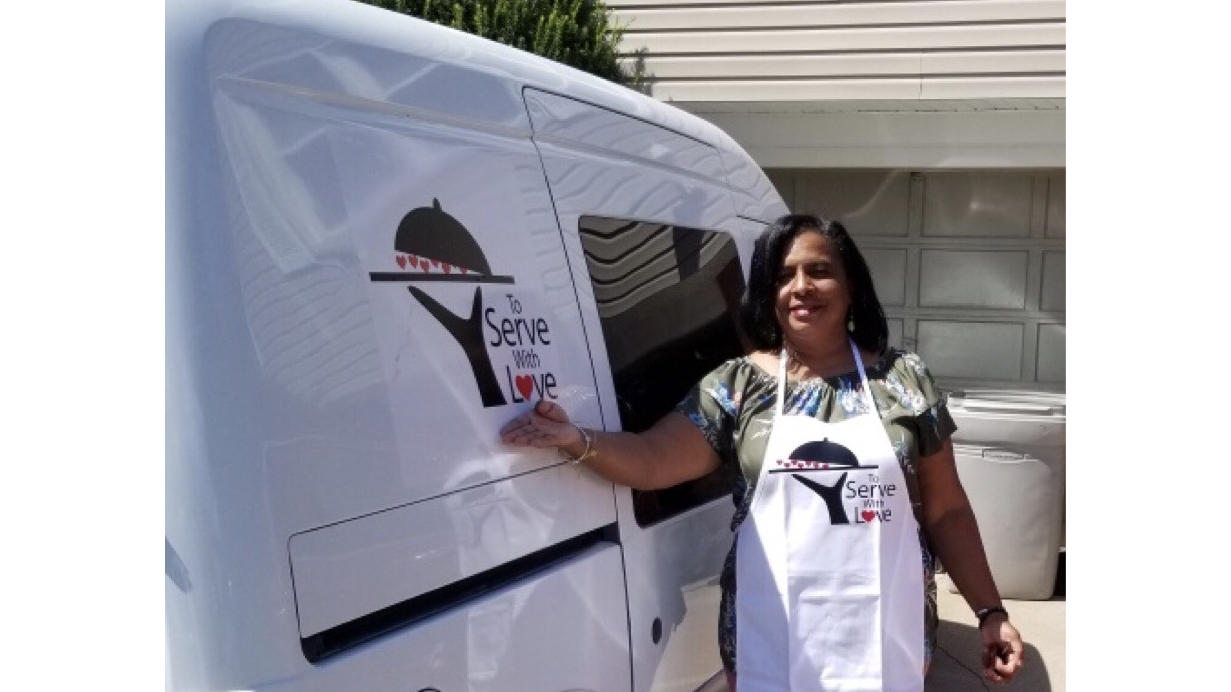 Diann Moore stands outside of her food delivery van