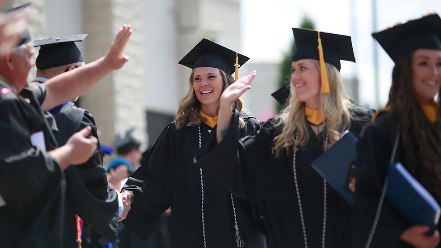 Two female Concordia graduates celebrate during the commencement recessional