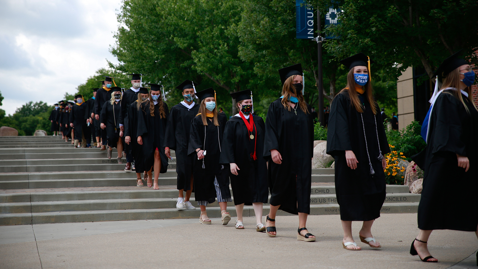 Concordia University, Nebraska Class of 2020 graduates walk through the plaza during the graduation processional.