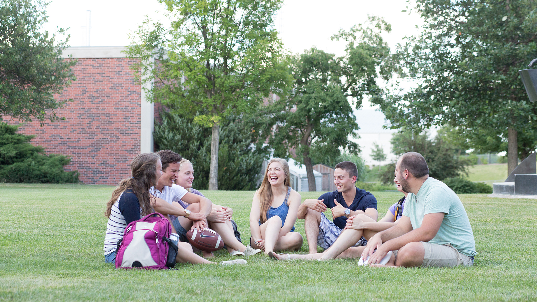 a group of Concordia students sit in the grass and visit in the quad