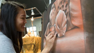 A female Concordia student adds finishing touches to her drawing of pink flowers.
